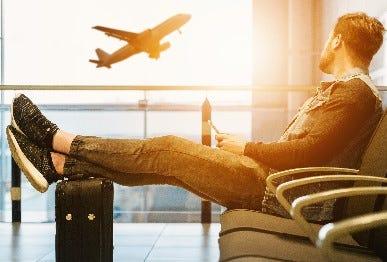 Mann an Flughafen mit Koffer