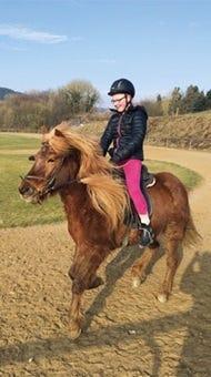 Finnja aktives Mädchen mit Typ-1 Diabetes auf dem Pferd