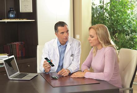 Arzt erklärt Patientin ein Blutzuckermessgerät
