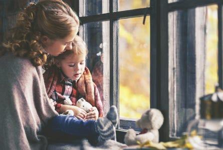 Mutter und Kind kuscheln am Fenster